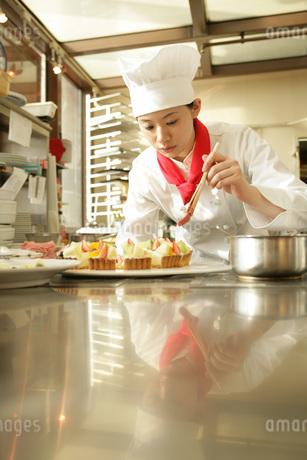 レストランの厨房で料理をする女性の写真素材 [FYI01829507]