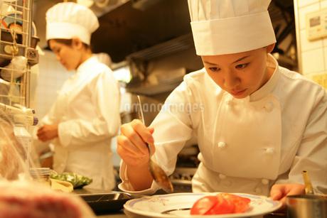 レストランの厨房で料理をする女性の写真素材 [FYI01829644]