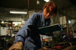 自動車整備工場で働く女性の写真素材 [FYI01829882]