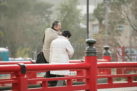 笑顔で町を歩く夫婦の写真素材 [FYI01830710]