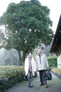笑顔で町を歩く夫婦の写真素材 [FYI01830794]