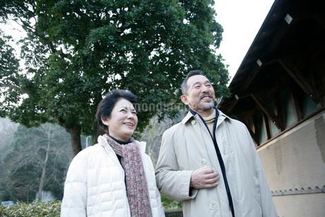 笑顔で町を歩く夫婦の写真素材 [FYI01831142]