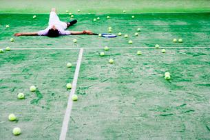 テニスコートで仰向けになる男性の写真素材 [FYI01832320]