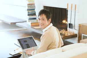 リビングでパソコンを楽しむ男性の写真素材 [FYI01832772]