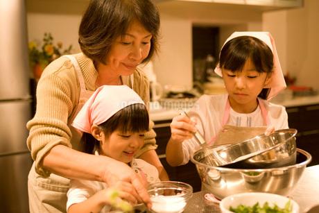 料理をする祖母と姉妹の写真素材 [FYI01833630]