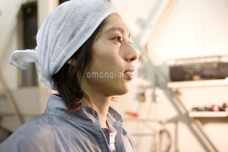 頭にタオルを巻く自動車整備士の写真素材 [FYI01834586]