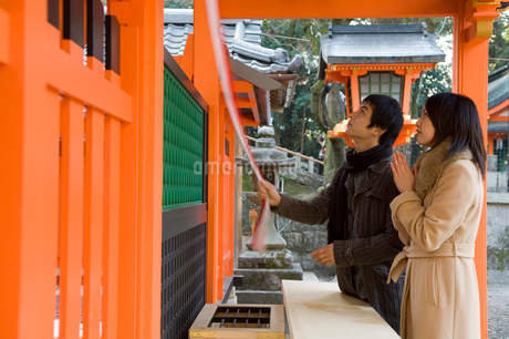 神社にお参りするカップルの写真素材 [FYI01836979]