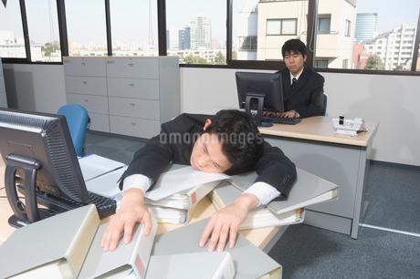 机に突っ伏すサラリーマンの写真素材 [FYI01840158]