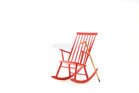 赤いロッキングチェアとステッキの写真素材 [FYI01843230]