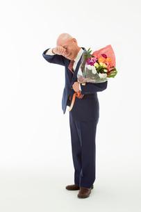 花束を持ち泣いている60代男性の写真素材 [FYI01846565]