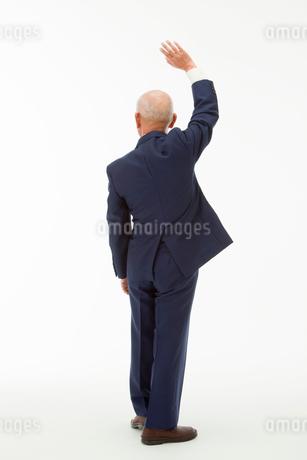 手を上げる60代男性の後ろ姿の写真素材 [FYI01846582]