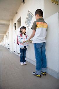 団地内の通路でファイルの受け渡しをする男の子と女の子の写真素材 [FYI01846804]
