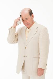 額の汗を拭う60代男性の写真素材 [FYI01847075]