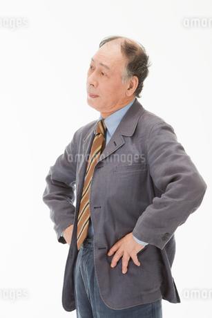 両手を腰に当てて悩む60代男性の写真素材 [FYI01847537]