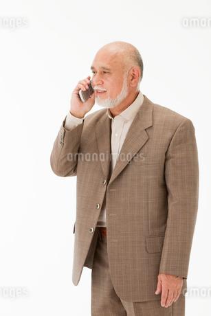 携帯電話で話す60代男性の写真素材 [FYI01847674]