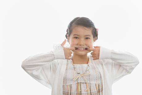 指で唇を左右に引っ張る女の子の写真素材 [FYI01848286]