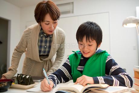 勉強する男子中学生と夜食を運ぶ母親の写真素材 [FYI01848305]