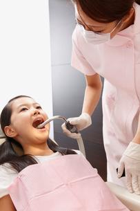 女の子の口腔内を洗浄する歯科助手の写真素材 [FYI01848475]