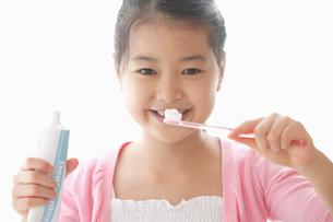 歯ブラシを持って見つめる女の子の写真素材 [FYI01848755]