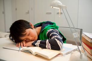 勉強に疲れてうたた寝をする男子中学生の写真素材 [FYI01848836]