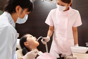 女の子の口腔内を洗浄する歯科助手の写真素材 [FYI01849204]