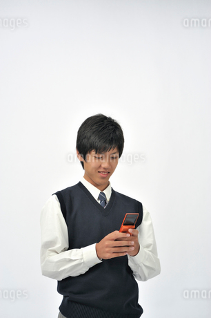 携帯電話を持つ男子高校生の写真素材 [FYI01849734]