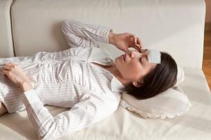 冷却ジェルシートを額に貼って寝る女性の写真素材 [FYI01849967]