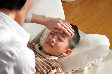 母親に額に手を当ててもらう男の子の写真素材 [FYI01849977]