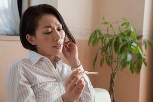体温計を持って眺める女性の写真素材 [FYI01850035]