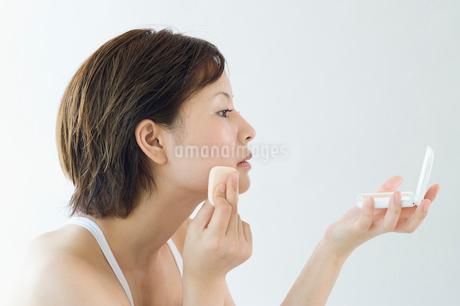 ファンデーションを塗る日本人女性の横顔の写真素材 [FYI01850934]