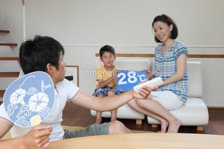 父に設定温度のボードを見せる母と子の写真素材 [FYI01851305]