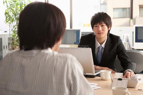 上司に話し掛けるスーツ姿の若い男性の写真素材 [FYI01851823]