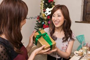 クリスマスパーティーでプレゼントを交換する女性の写真素材 [FYI01853644]