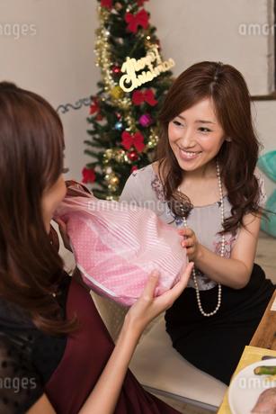 クリスマスパーティーでプレゼントを交換する女性の写真素材 [FYI01853994]