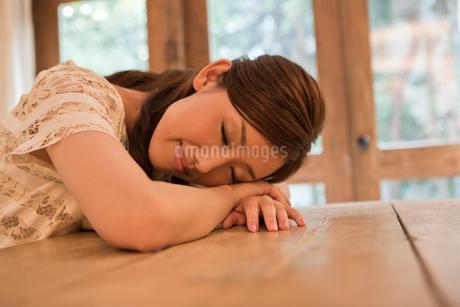 テーブルでうたた寝をする女性の写真素材 [FYI01855470]
