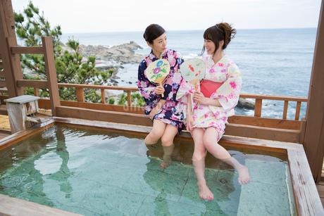 露天風呂で足湯を楽しむ浴衣姿の女性2人の写真素材 [FYI01856356]