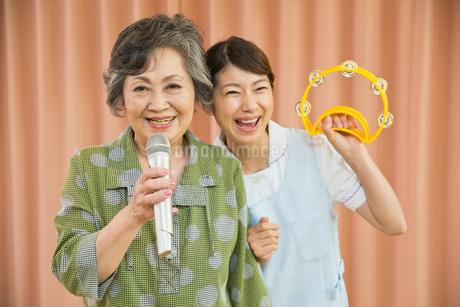 カラオケを楽しむシニア女性と介護福祉士の写真素材 [FYI01856402]