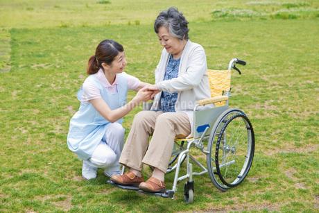 車いすに乗るシニアの手を握る介護福祉士の写真素材 [FYI01856420]