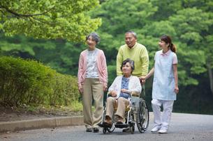 公園を散歩するシニアの男女と介護福祉士の写真素材 [FYI01856426]
