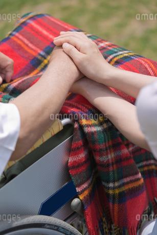 車いすに乗るシニアの手を握る介護福祉士の写真素材 [FYI01856490]