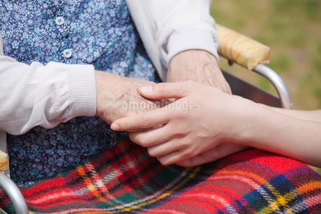 車いすに乗るシニアの手を握る介護福祉士の写真素材 [FYI01856515]