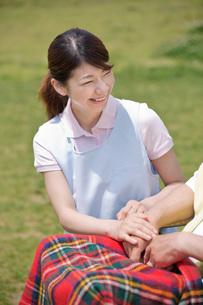 車いすに乗るシニアの手を握る介護福祉士の写真素材 [FYI01856550]