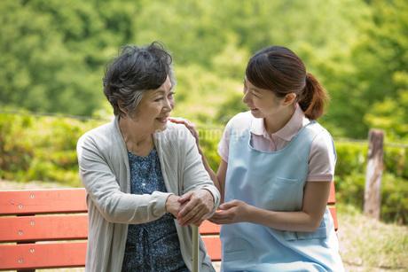 公園のベンチで話すシニア女性と介護福祉士の写真素材 [FYI01856574]