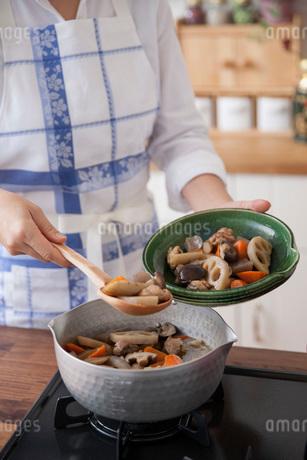 筑前煮を鍋から皿へ盛り付ける女性の写真素材 [FYI01856631]