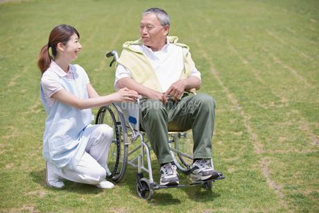 公園で休む車いすのシニア男性と介護福祉士の写真素材 [FYI01856642]