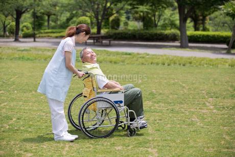 シニア男性の車いすを押す介護福祉士の写真素材 [FYI01856673]