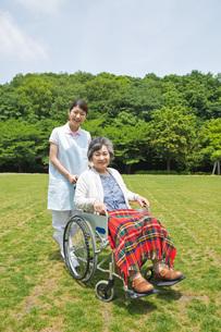 シニア女性の車いすを押す介護福祉士の写真素材 [FYI01856804]