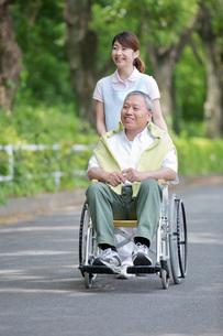 シニア男性の車いすを押す介護福祉士の写真素材 [FYI01856863]