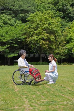 公園で休む車いすのシニア女性と介護福祉士の写真素材 [FYI01856880]
