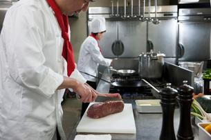 ステーキ用の肉を切る調理師の写真素材 [FYI01856929]